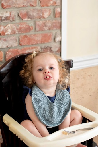 Toddler in highchair with a hand-knit bib and cheerio in her mouth.