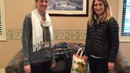photo of two women with bags of donated items