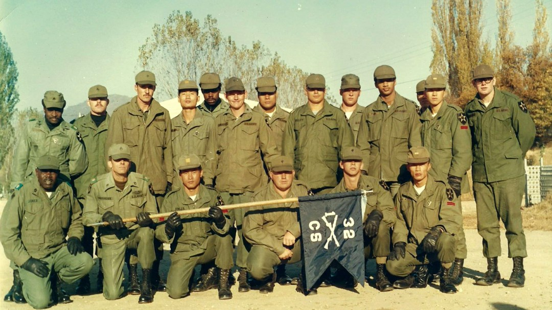 Steve Bailey, (standing behind the flag), is pictured here with his platoon in the 1970s.