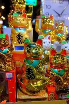 Goldene Katzen winken den Reichtum heran.