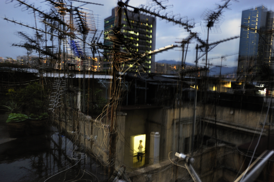 A shanty town of corrugated metal shacks atop a Kwun Tong factory building. Hong Kong's overwhelming density (6782.9 people per square kilometer in 2010) and lack of affordable housing mean that even such crummy homes can charge unexpectedly high rent.