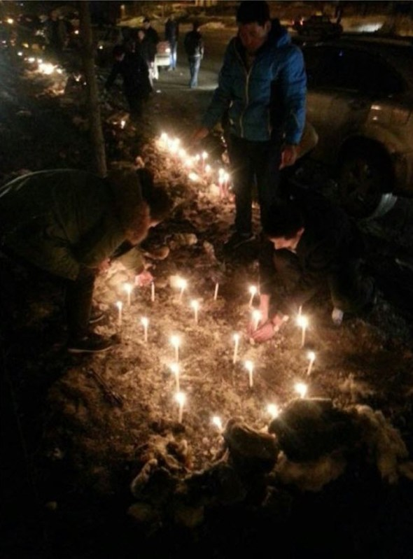 Candles and mourners outside the home of the dead infant's family home.
