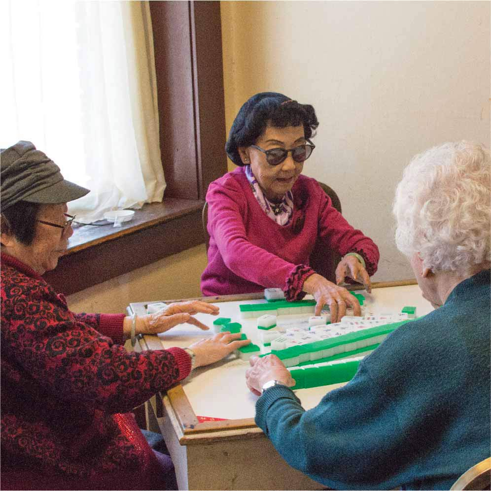three chinese seniors around a table playing Mahjong. The women in the middle has black hair done in a 50s like manner and is wearing Pantos shaped sunglasses, a pink sweater and pink ascot. She has her hands out on the table to grab a tile.