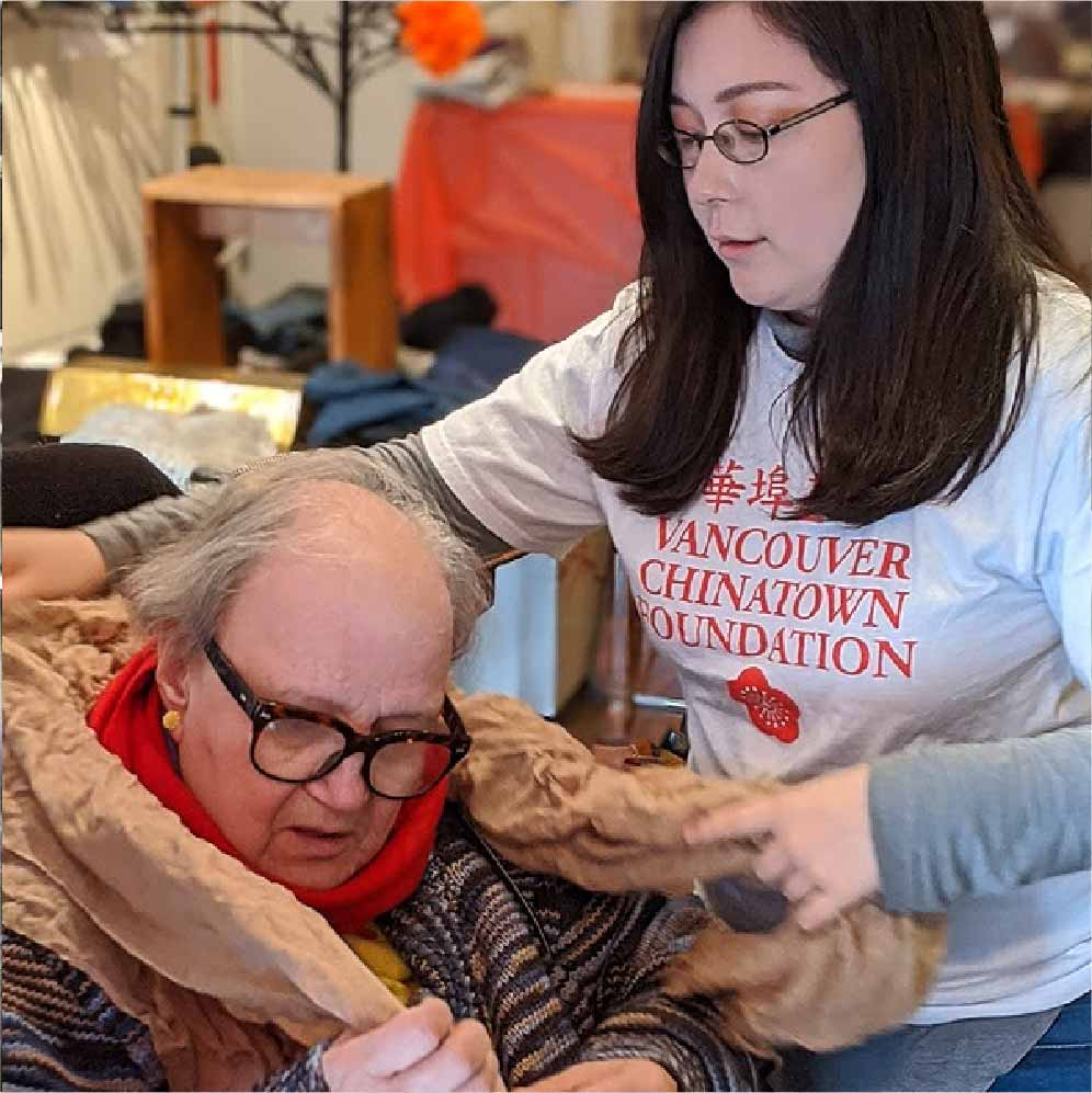 A young woman helping an older woman try on a scarf. The younger woman is on the right side of the photograph and is wearing a Vancouver Chinatown Foundation volunteer t-shirt, glasses, and a long sleeve shirt. The older woman is on the left and is wearing glasses and a large puffy jacket. The volunteer is helping her put on an orange scarf
