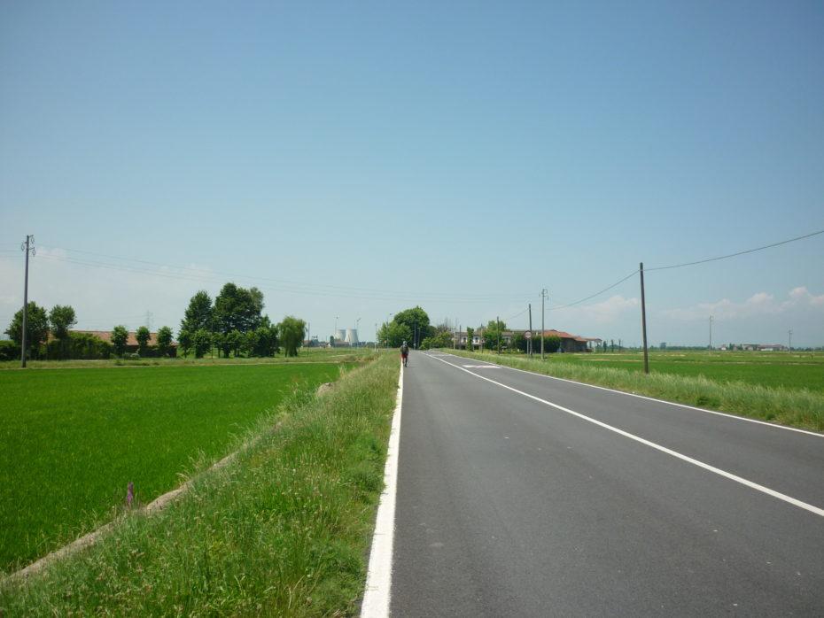 Strada asfaltata che ci porterà a Castell'Apertole, tra risaie e sole.