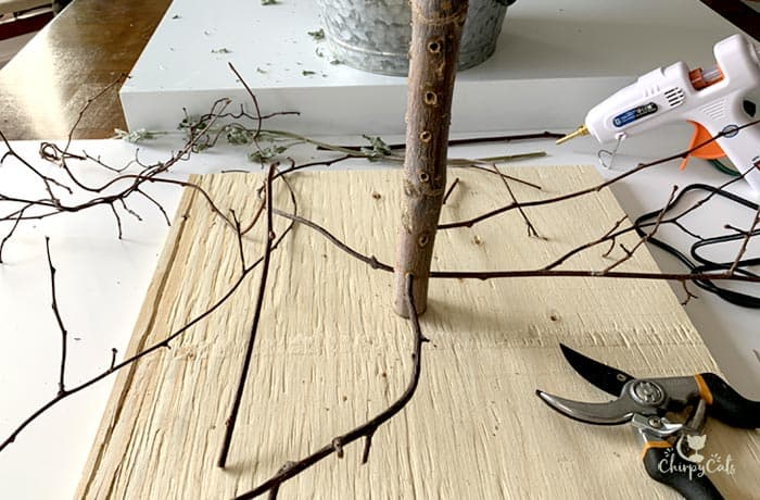 making a Christmas tree for cats glueing the branches into the holes.