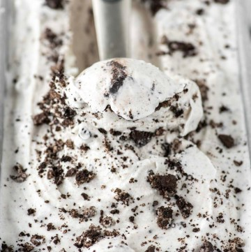cookies and cream ice cream being scooped out of metal tin