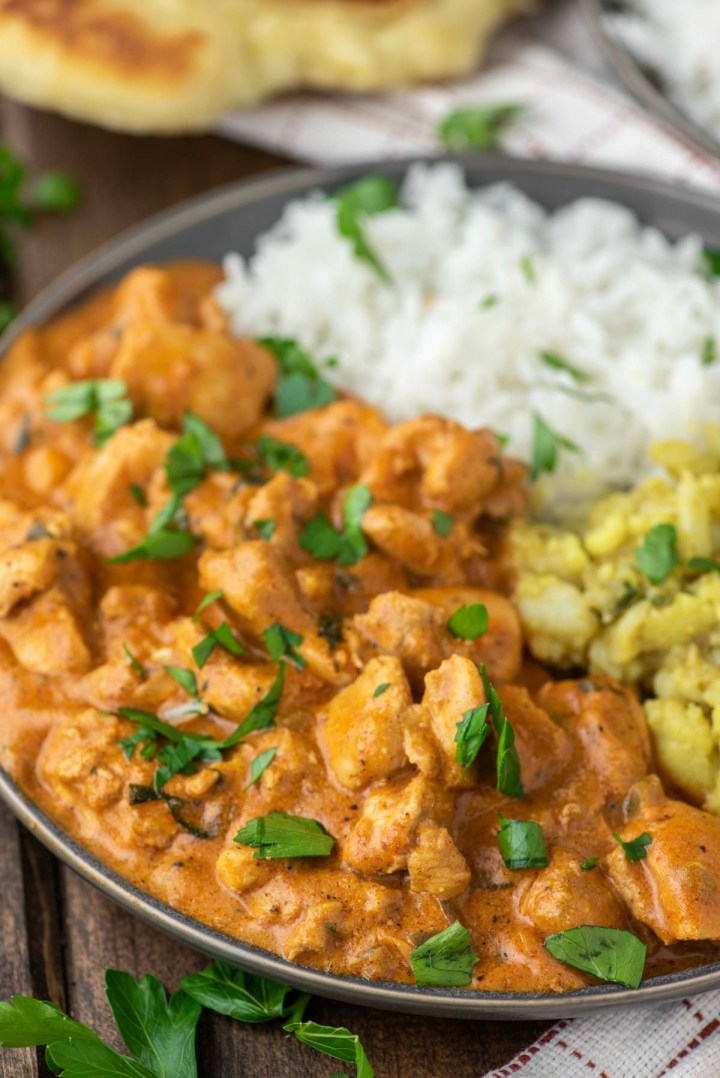 chicken masala on grey plate with aloo gobi and white rice