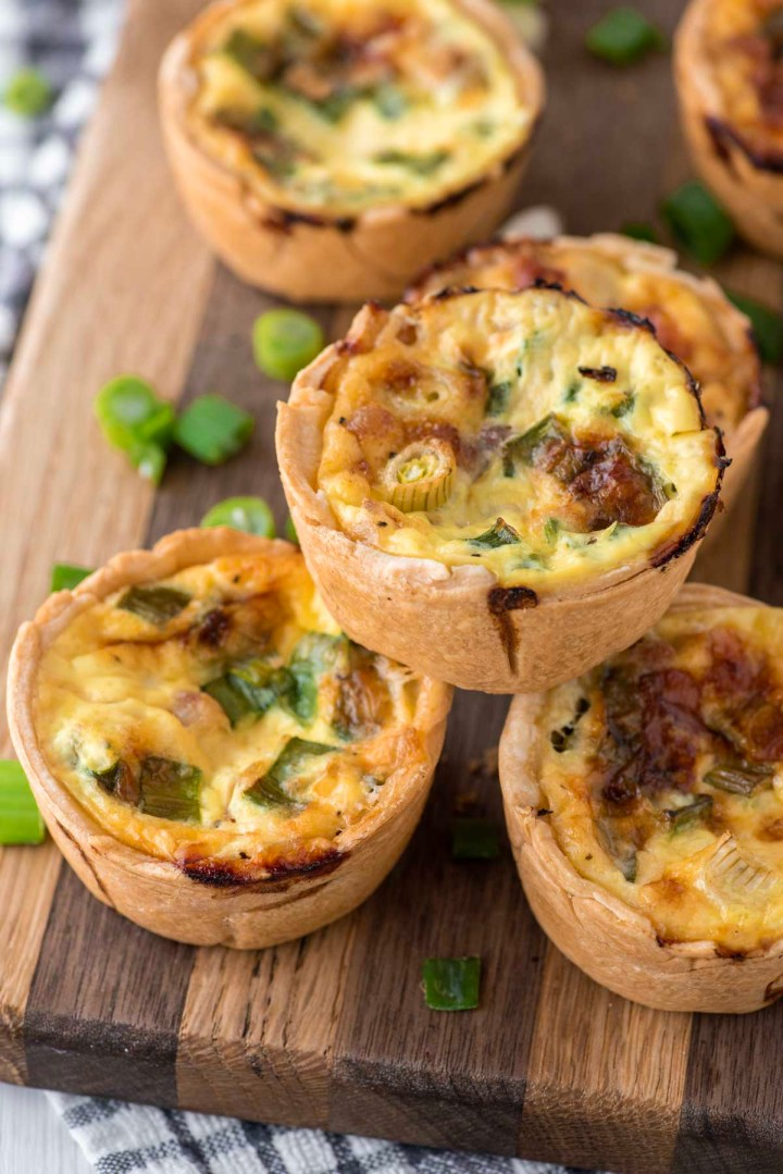 mini ham and cheese quiche stacked on cutting board