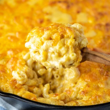 spoonful of baked cheddar mac and cheese pulled from skillet