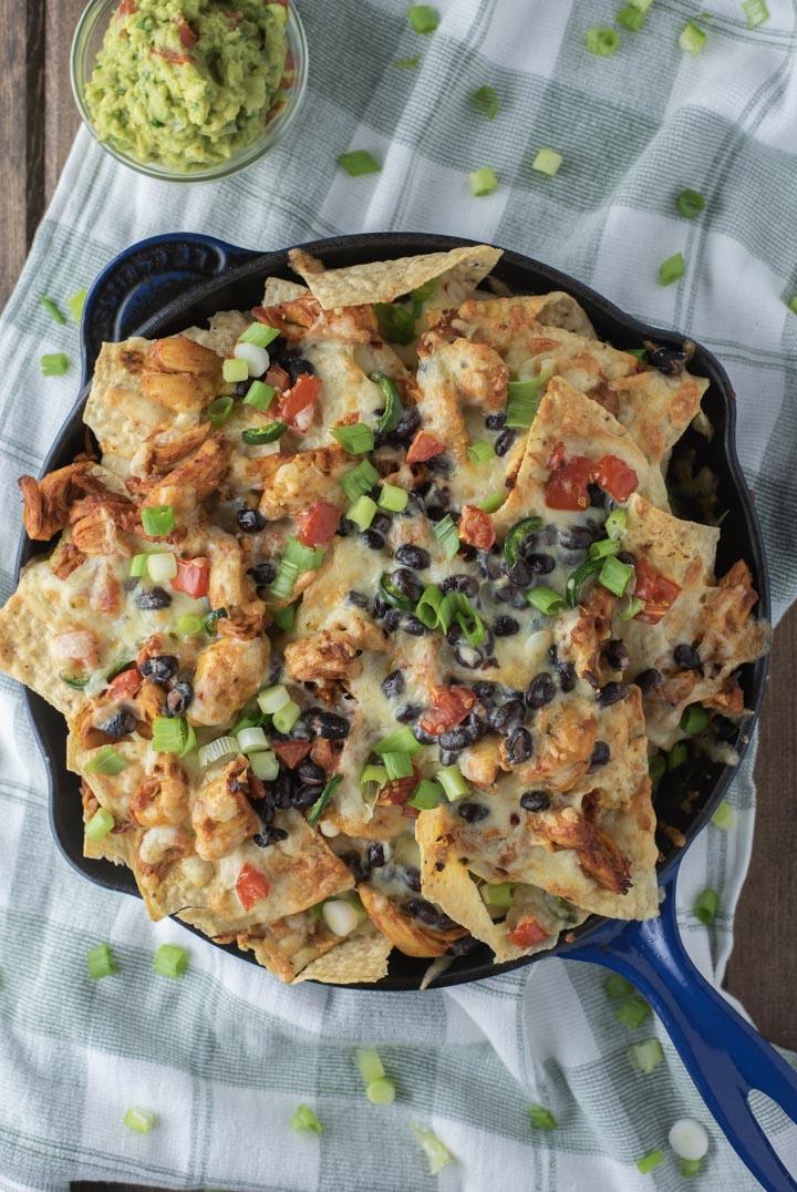 overhead shot of chicken nachos in cast iron skillet