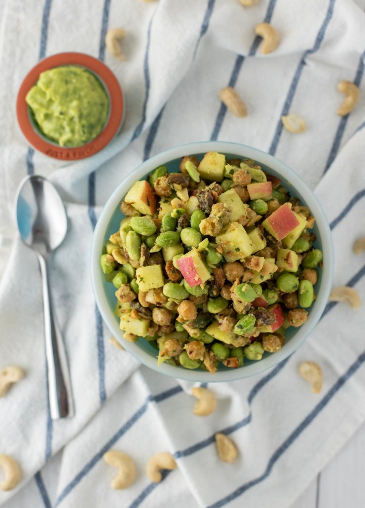 overhead shot of edamame salad in blue bowl with side of avocado dressing