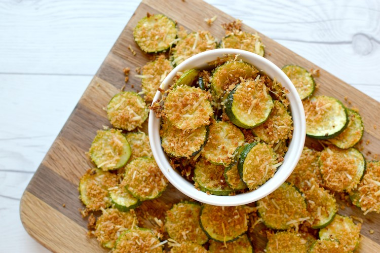 Overview of baked parmesan zucchini chips in small bowl on wood cutting board