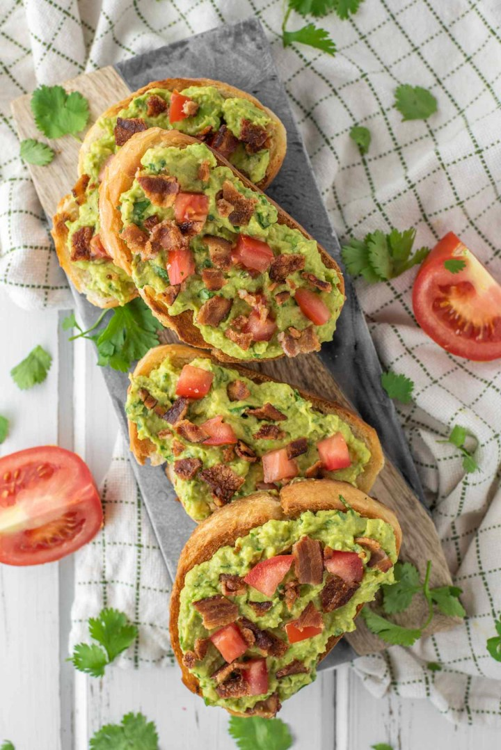 overhead shot of 4 slices of bacon avocado toast on cutting board
