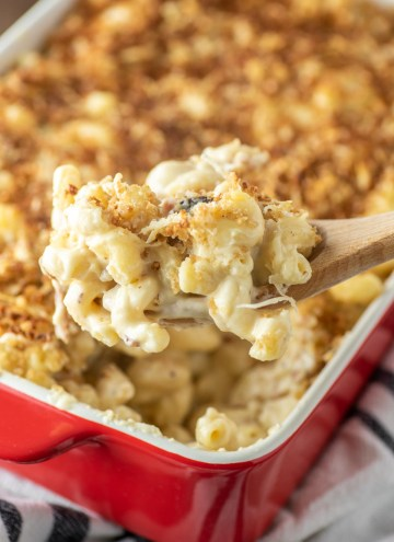 wood spoon pulling out smoked gouda bacon mac and cheese from baking dish