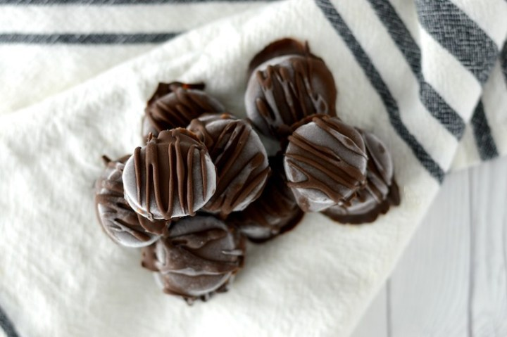 overlay of stacked chocolate peanut butter banana bites on kitchen towel
