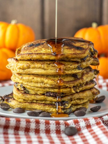close-up of stacked pumpkin chocolate chip pancakes on white plate