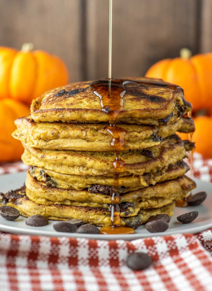 maple syrup being drizzled on stack of pumpkin chocolate chip pancakes
