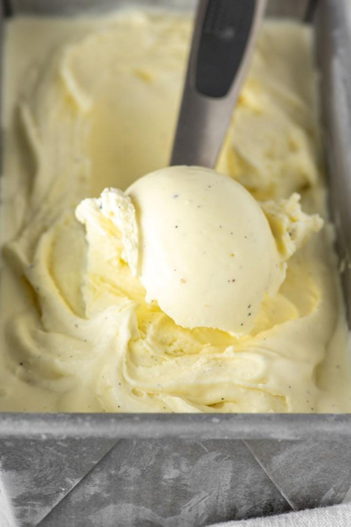close-up of vanilla bean ice cream in orange bowl