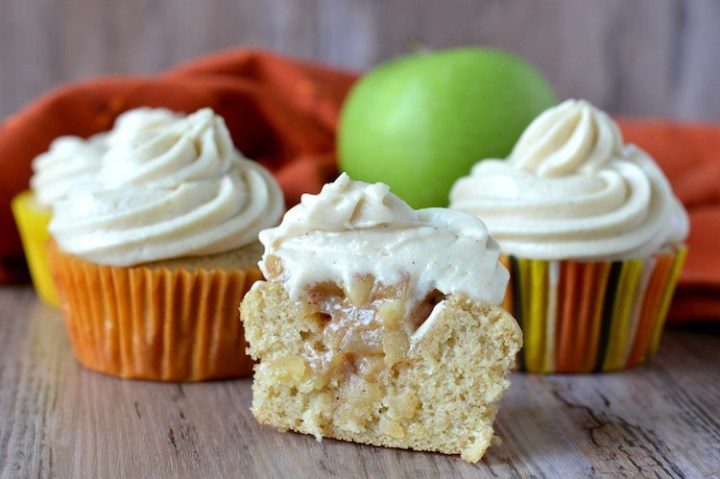 close-up of four apple pie cupcakes with one cupcake cut open