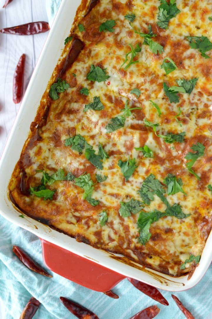 overhead shot of veggie enchiladas in red baking dish