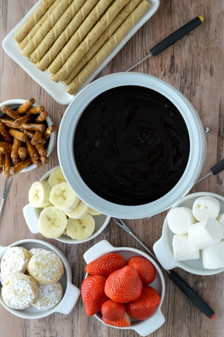 overhead shot of dark chocolate fondue in white pot with dippers around it