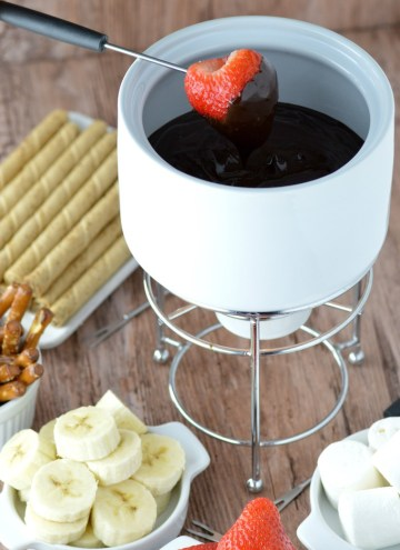 close-up of strawberry dipped in dark chocolate fondue