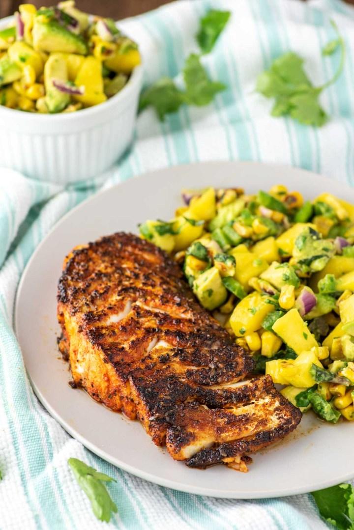 blackened cod with corn mango salsa on plate with dish towel