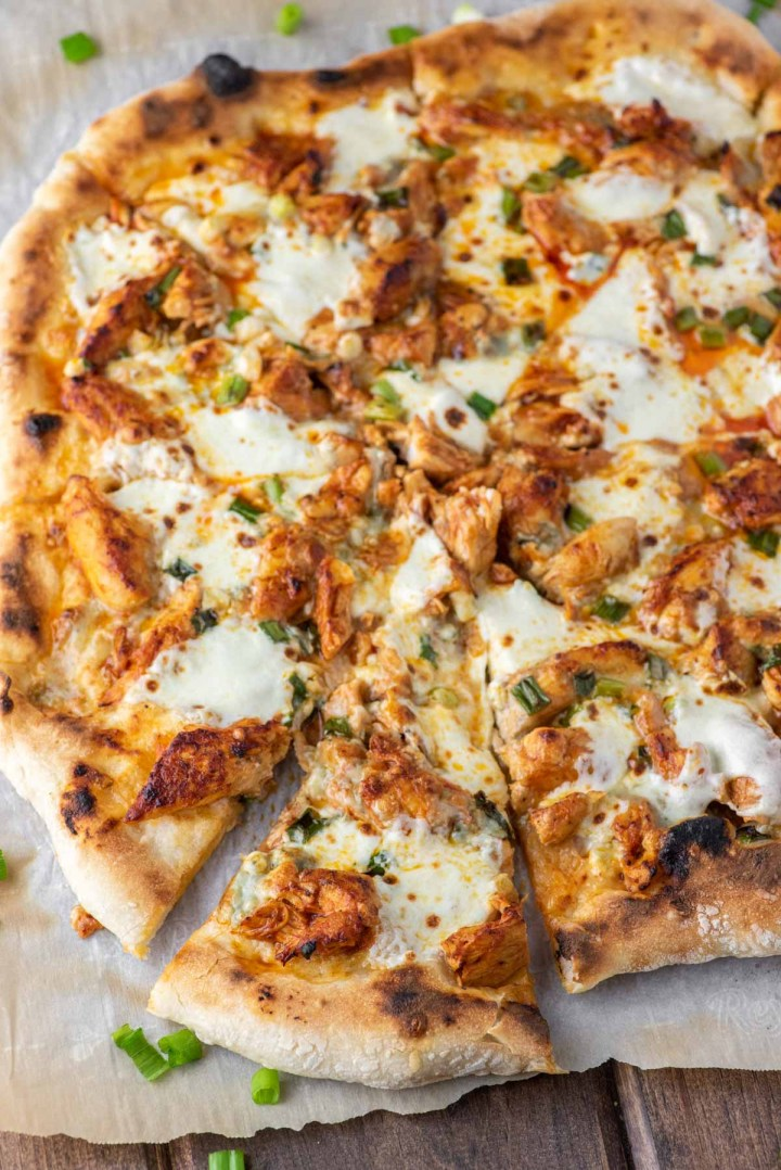 slice of buffalo chicken pizza pulled on parchment paper