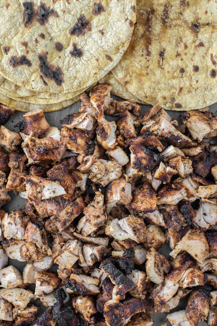 overhead shot of chopped grilled chicken with corn tortillas