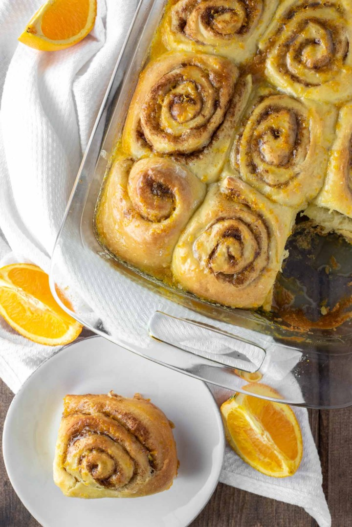overhead shot of orange rolls in baking dish and on white plate