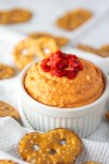 roasted red pepper hummus in white ramekin with pretzel chips