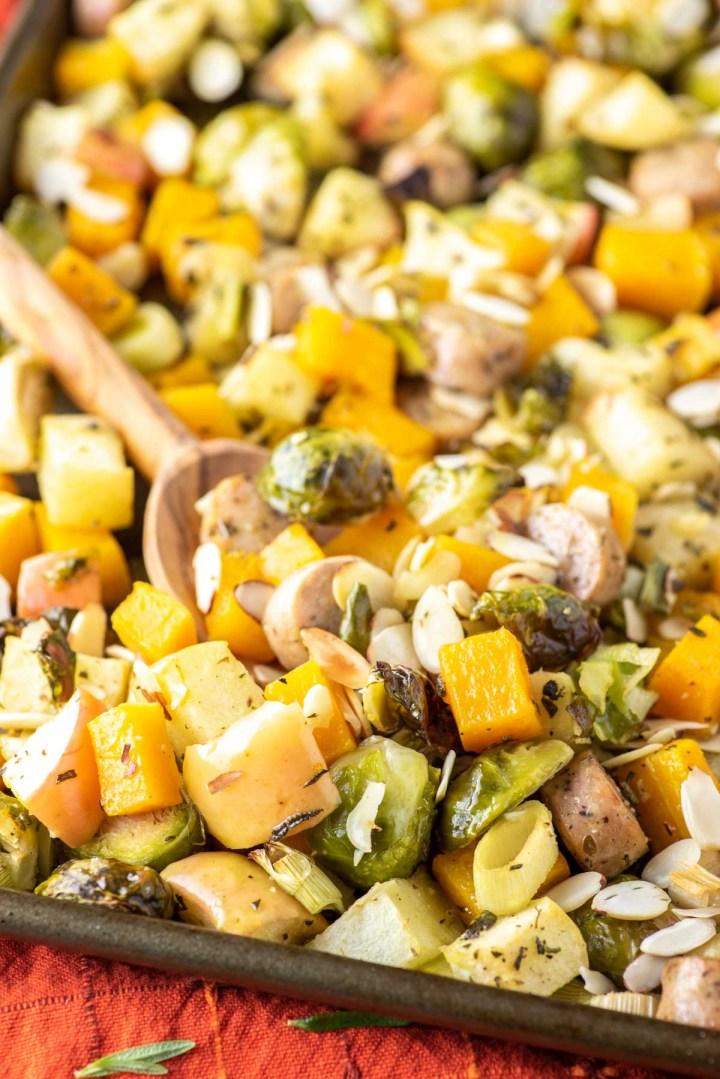 spoon dipped in autumn sheet pan sausage and veggies