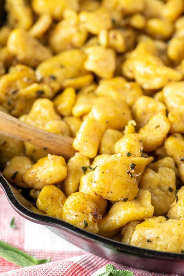 spoon dipped in butternut squash gnocchi