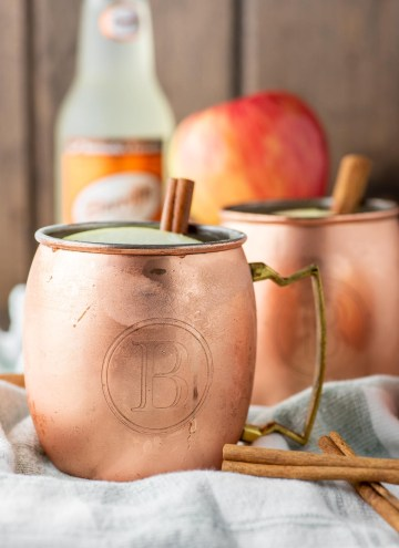 two apple cider moscow mules in copper cups