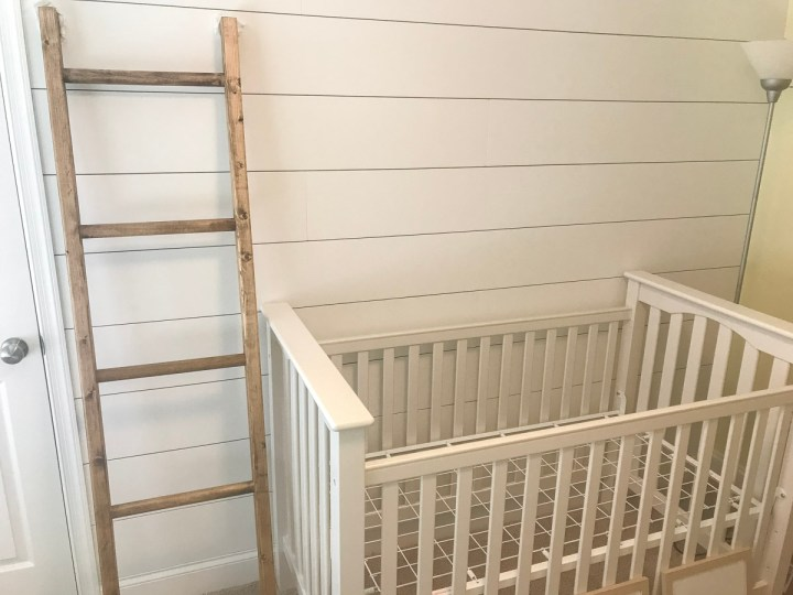 blanket ladder against shiplap wall with crib