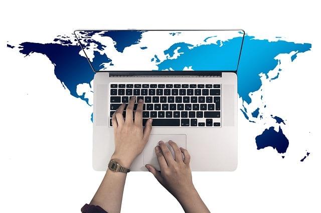 地球とパソコンとキーボードを押す手