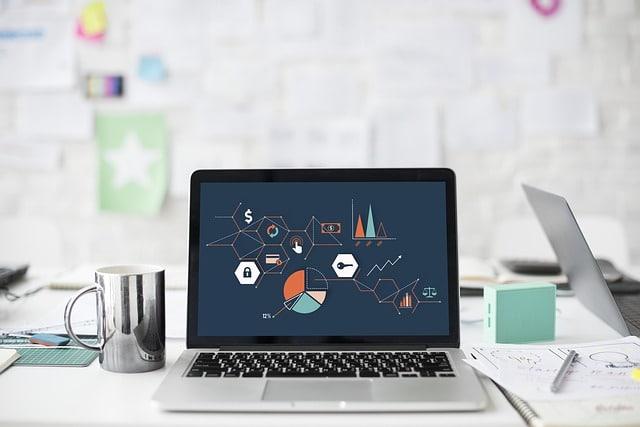 分析画面が表示されたパソコンとコーヒーとその他文房具