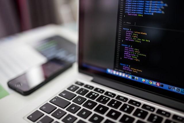 パソコンの画面に表示されたプログラミングのコードと横に置かれたスマートフォン
