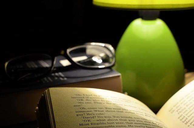 ランプの光に照らされたメガネと開かれた本