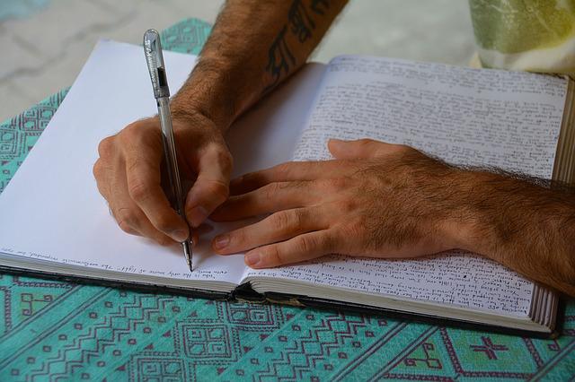 開かれたノートとそこにペンでメモをする男性の手