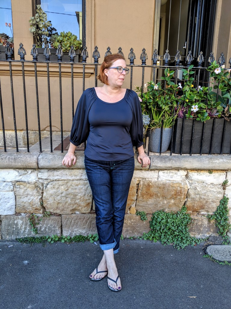 The author leaning against a wall looking away from the camera.  She is wearing a dark blue top with voluminous sleeves and blue rolled up jeans.