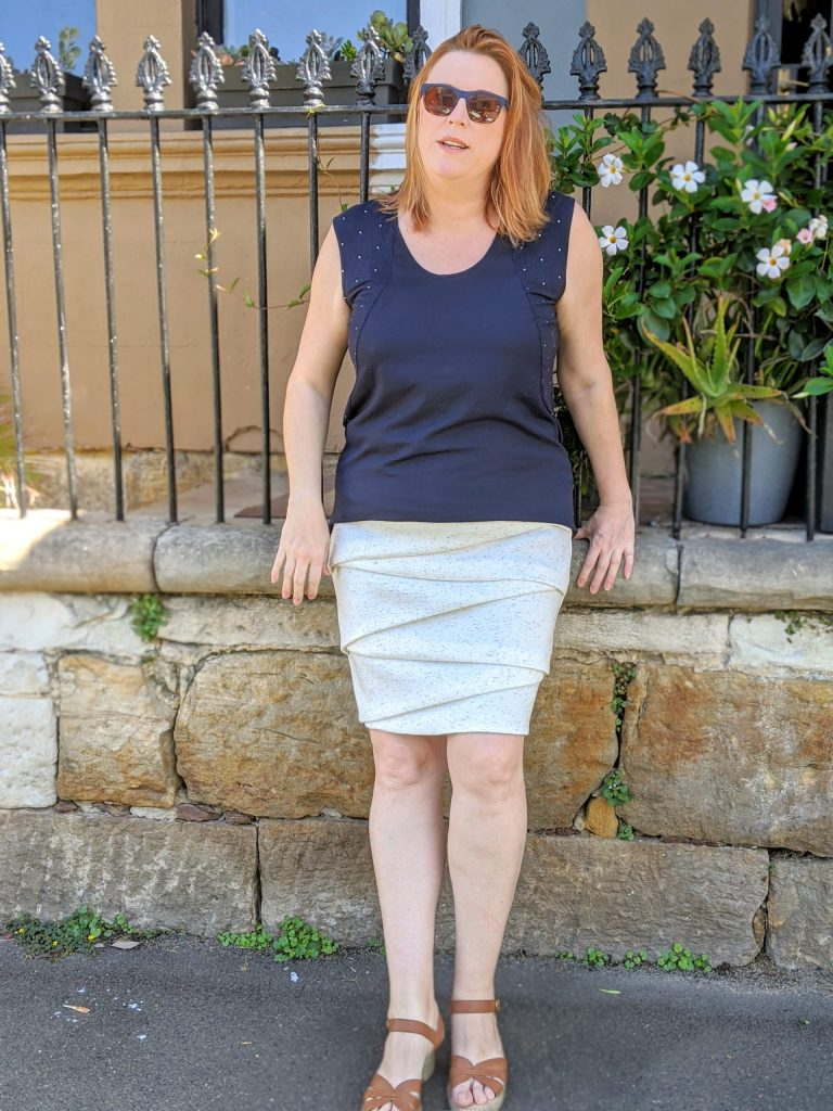 Author standing in front of a sandstone wall and black railing wearing a blue top, a cream folded knit skirt and sunglasses.