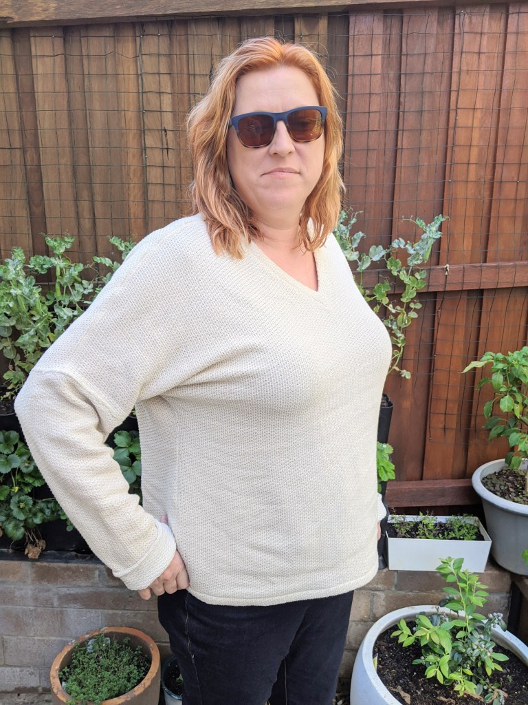 The author is standing in her back yard.  She is wearing jeans and a cream coloured v-neck sweater with the long sleeves cuffed.  She is wearing sunglasses and looking at the camera.