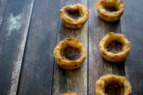Six Canadian butter tarts in two vertical lines across a dark wood table.