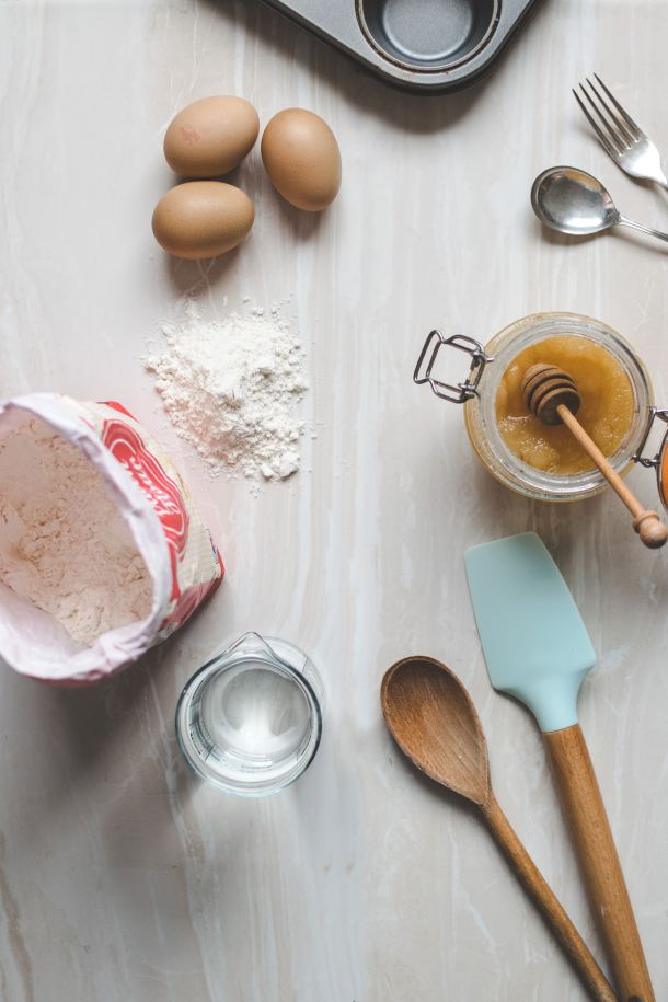 An overhead photo of baking utensils, honey and flour.