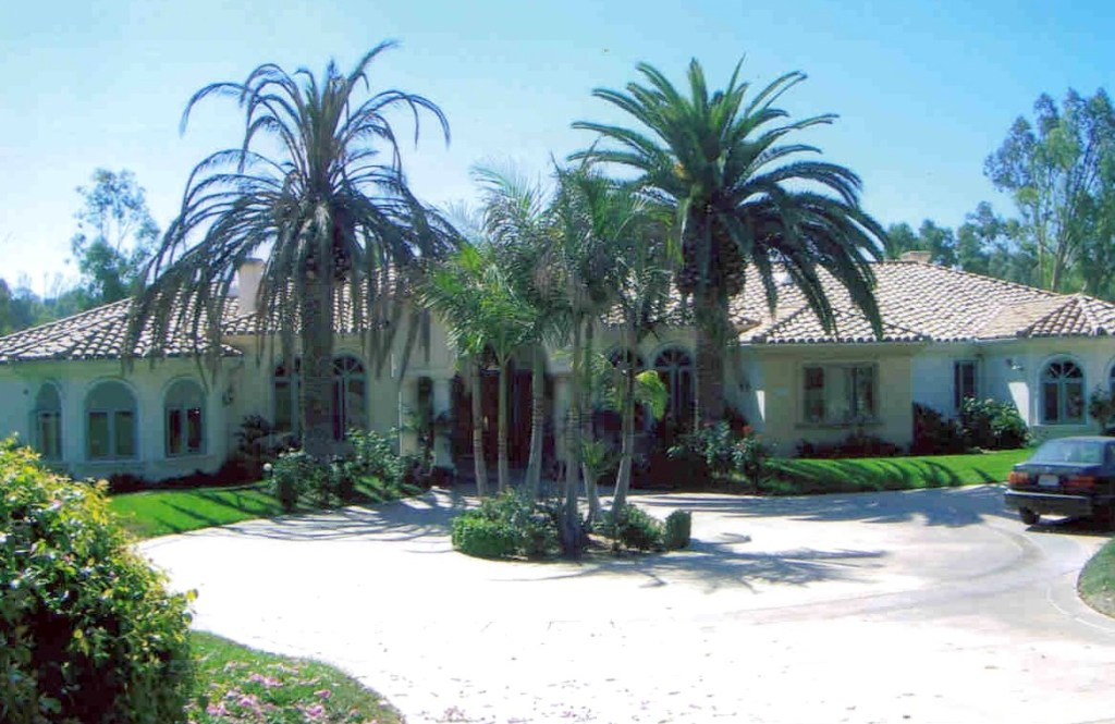 Front entrance obscured by palms