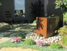 A fountain and a chair placed by the front door take advantage of a shady tree.