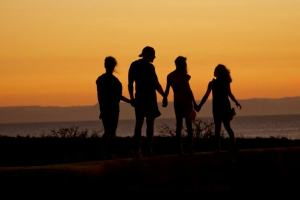 family standing in the sunset