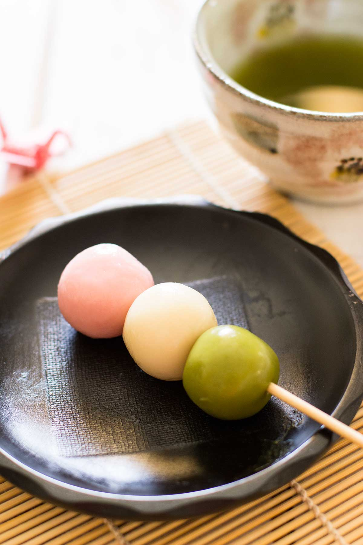 usually hishi mochi a type of rice cake mochi made into a diamond shape with three different coloured tiers of pink green and white are displayed on